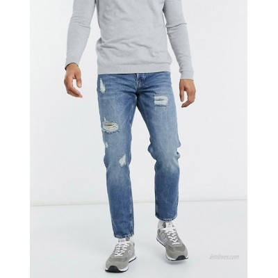 DESIGN tapered jeans in vintage mid wash blue with heavy rips
